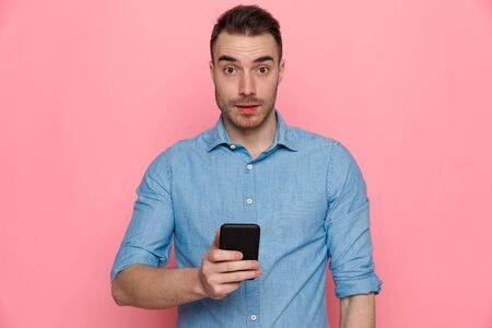 surprised casual man standing and looking at camera with his phone on his hand on pink studio background