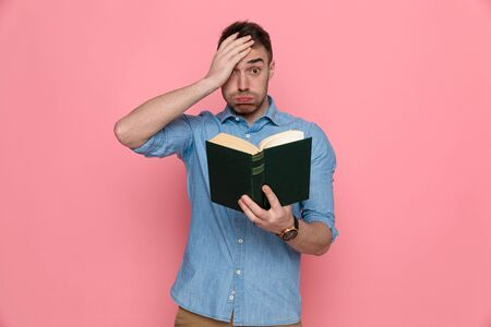 young casual man slapping his head, holding his book and blowing cheeks on pink studio background 版權商用圖片
