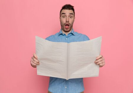 attractive young casual man holding the newspaper, looking at camera with mouth open, shocked by the news on pink studio background