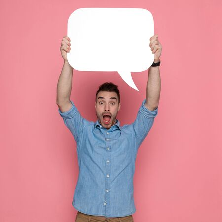 handsome shocked casual man holding a speech bubble overhead on pink studio background