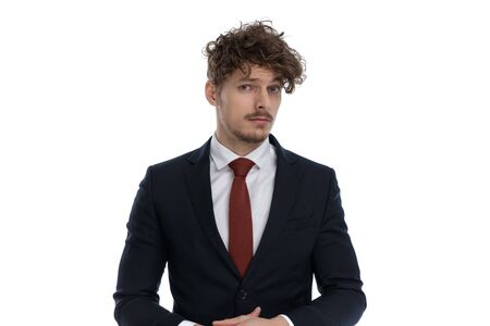 Focused businessman looking forward disagreeing while wearing suit and standing on white studio background