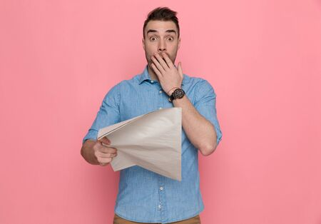 young casual man covering his mouth, being shocked by the news read from the newspaper on pink studio background