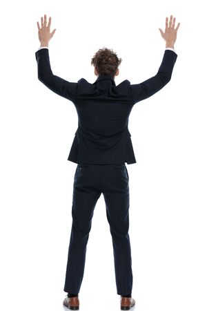 Rear view of guilty businessman freezing as being caught by police while wearing suit and standing on white studio background