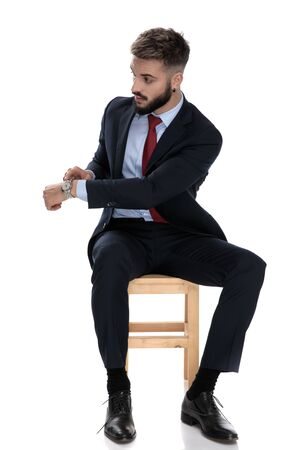 young businessman in suit showing clock to side on watch, sitting isolated on white background