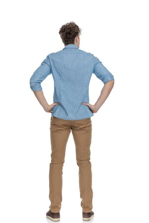back view of young guy in denim shirt holding hands on hips, standing isolated on white background, full body
