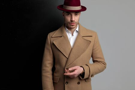 attractive young model wearing long coat and hat, holding hands in a fashion pose and standing on black grey background Stock Photo