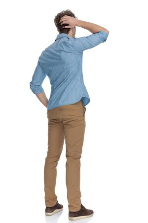 back view of casual guy scratching head, trying to solve difficult problems, isolated on white background, full body