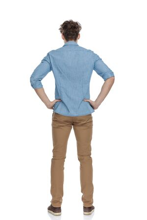 back view of thoughtful casual guy holding hands on hips and thinking, standing isolated on white background, full body Foto de archivo