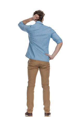 back view of casual man scratching head and thinking of ways to solve difficult problems, standing isolated on white background, full body