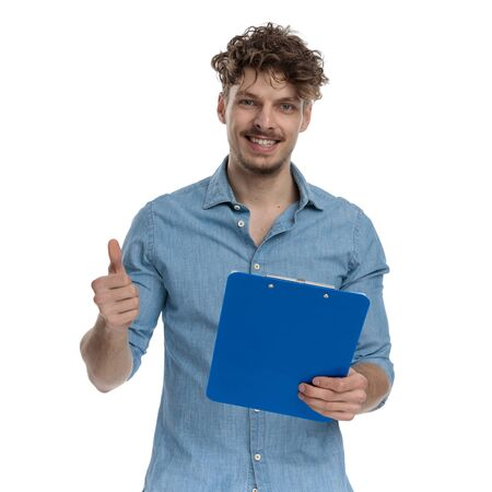 happy young guy making thumbs up sign and holding clipboard, smiling and standing isolated on white background, portrait