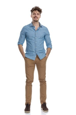 attractive casual guy in denim shirt holding hands in pockets and smiling isolated on white background, full body Фото со стока