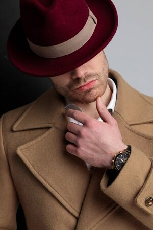 mysterious young guy in long coat, wearing hat, touching chin in a fashion way and looking to side, standing on black grey background Foto de archivo