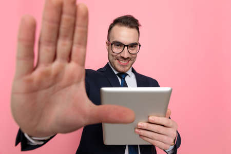 upset young man in suit holding fist up, pointing finger and threatening, standing on pink background