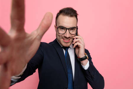 young businessman in suit covering face with big red heart and standing on pink background