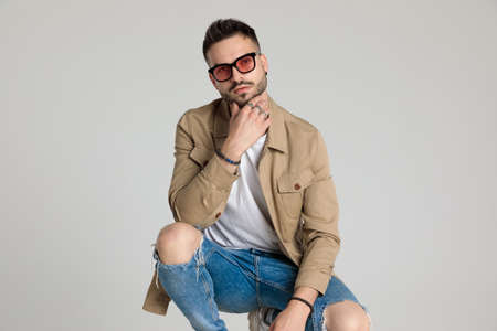 thoughtful young casual man in jacket wearing sunglasses, touching chin and thinking, holding elbows on knees and crouching on grey background
