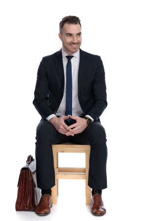Excited businessman playing with his hands and looking away beside briefcase while sitting on a chair on white studio background