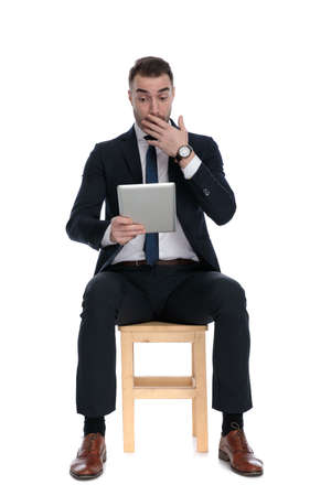 Surprised businessman holding tablet and gasping, covering his mouth while sitting on a chair on white studio background