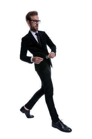 elegant young man in black suit looking to side and confidently marching on white background, full body