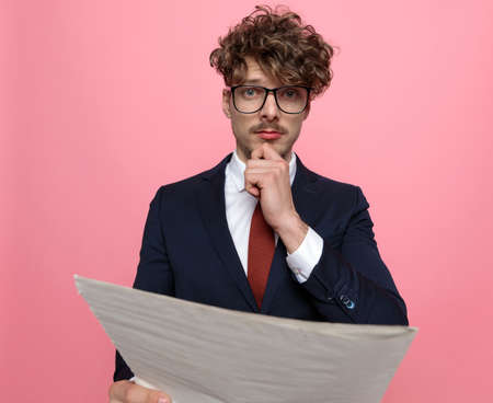 young elegant businessman in navy blue suit wearing glasses, holding hands to chin and thinking, reading newspaper on pink background
