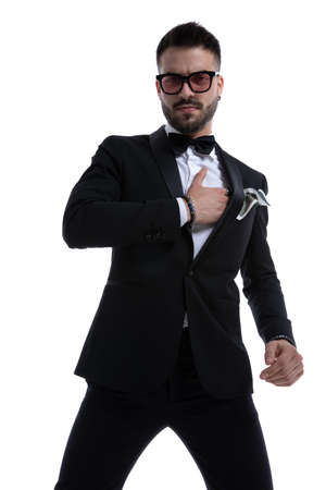 dramatic unshaved man in tuxedo holding hands on chest and posing isolated on white background
