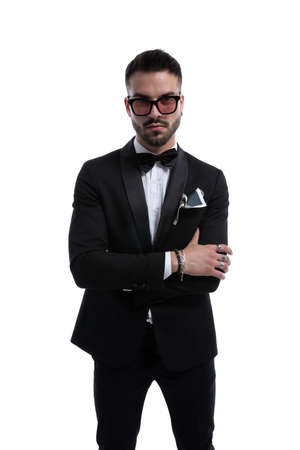 cool businessman in tuxedo wearing sunglasses crossing arms standing isolated on white background