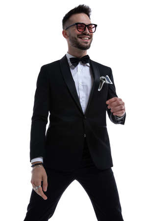 happy elegant man in tuxedo looking to side and smiling holding hands in a fashion pose isolated on white background Stock Photo