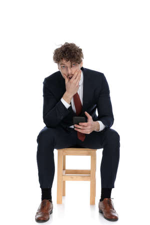 handsome shocked businessman covering his mouth and holding a phone, sitting on white background