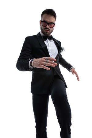 dramatic cool guy in tuxedo holding knee in a fashion pose, kicking and moving isolated on white background