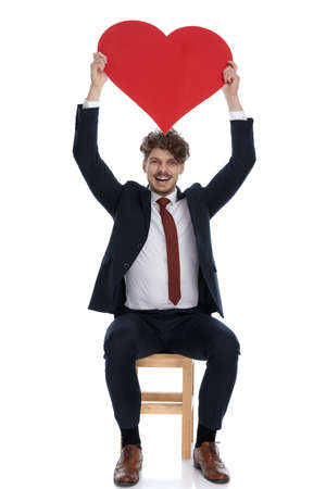 excited businessman holding a big red heart overhead and sitting on white background
