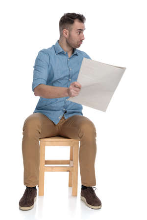 Impressed smart casual man holding newspaper and discussing while sitting on a chair on white studio background
