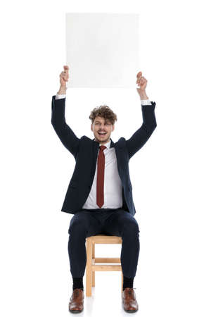businessman holding a blank billboard overhead and sitting against white background