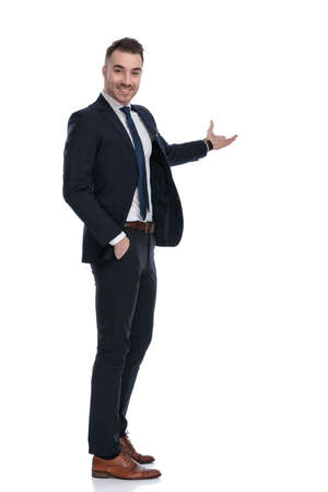 Side view of confident businessman smiling and presenting while standing on white studio background