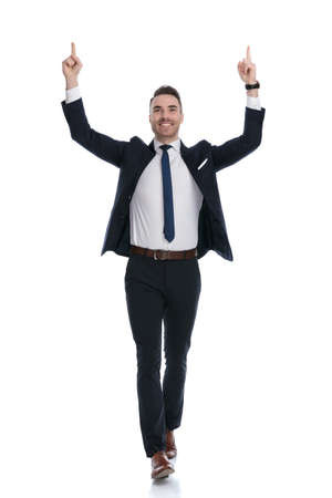 Cheerful businessman celebrating and pointing up with both hands while walking on white studio background Stock Photo