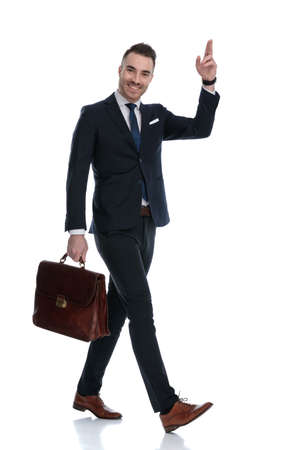 Side view of positive businessman greeting and holding briefcase while walking on white studio background Banque d'images