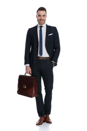 Positive businessman holding briefcase and smiling with hand in pocket while standing on white studio background Banque d'images
