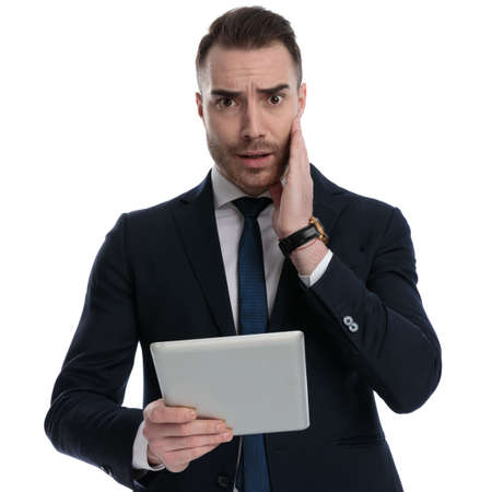 Worried businessman holding tablet and frowning while standing on white studio background