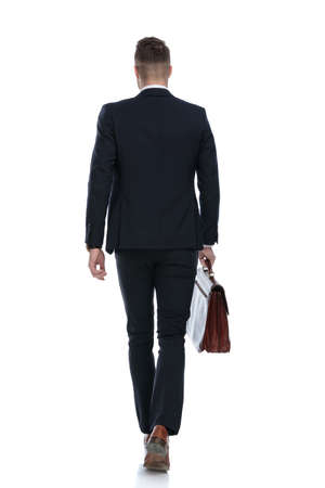 Rear view of businessman holding briefcase and walking on white studio background