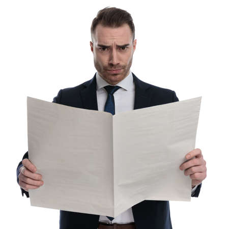 Upset businessman reading newspaper and frowning while standing on white studio background