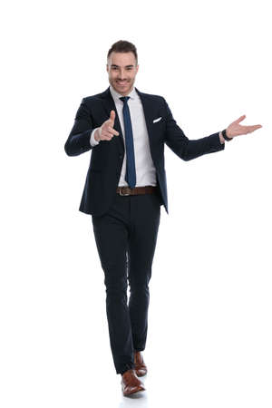 Smiling businessman pointing and presenting while walking on white studio background