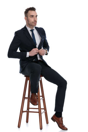 Serious businessman opening his jacket and looking away while sitting on a stool on white studio background