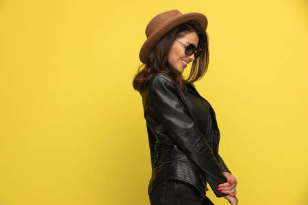 shy young girl in leather jacket looking down and holding hands on yellow background Stock Photo