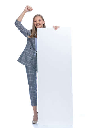 enthisiastic young girl in blue checkered suit holding arm in the air and cheering, presenting empty board and smiling, sitting isolated on white background, full body