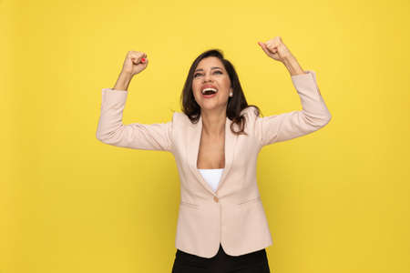 happy young businesswoman in pink suit holding arms in the air and celebrating, looking up, laughing and standing on yellow background