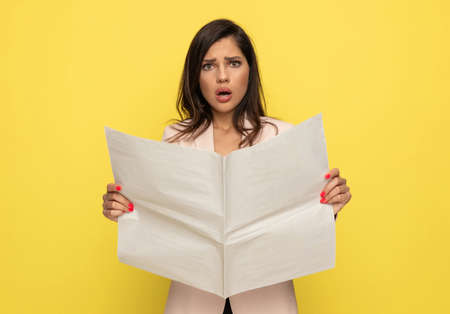 upset young woman in pink suit opening mouth in a shocked manner and reading newspaper, standing on yellow background