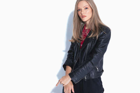 Charming fashion model gesturing being arrested and wearing leather jacket while standing on white studio background Stockfoto