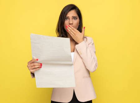 shocked young girl in pink suit reading newspaper, covering mouth in a surprised manner on yellow background