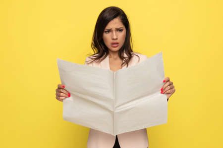 frustrated young businesswoman in pink suit holding and reading newspaper on yellow background