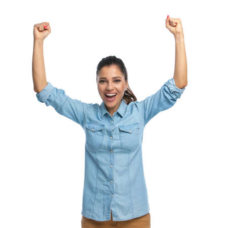 Cheerful smart casual woman shouting and celebrating, standing on white studio background