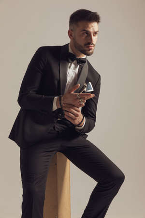 Eager groom holding hands together and curiously looking away, wearing tuxedo while sitting on gray studio background