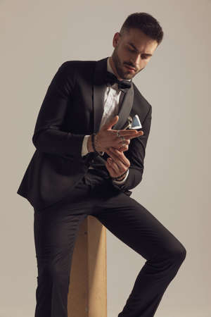 Pensive groom holding hands together and looking at them, wearing tuxedo while sitting on gray studio background